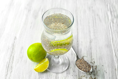Glass of water with chia seeds and lime slices on table