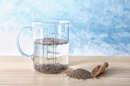 Measuring cup of water with chia seeds on table