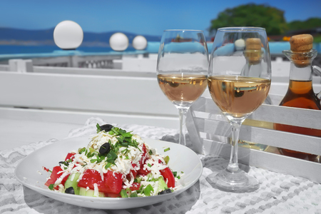 Two glasses of white wine and plate with exotic salad on table outdoors