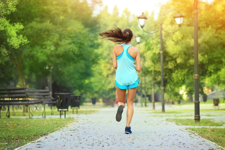 Morning of young sporty woman running in park