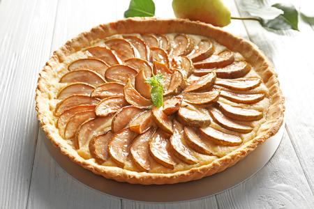 Tasty pear tart on white wooden table