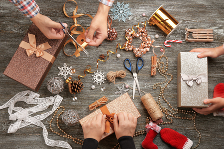 Family preparing decor for Christmas gifts on wooden background