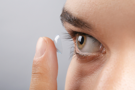 Young man putting contact lens in his eye on grey background, closeup Standard-Bild
