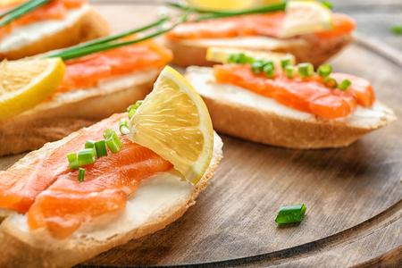 Delicious salmon bruschettas on wooden board, closeup