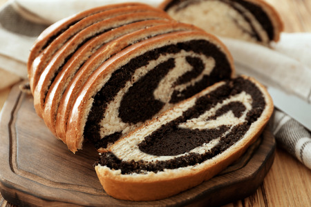 Tasty pastry with poppy seeds on wooden board