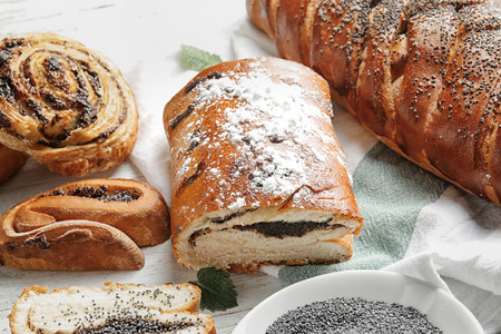 Tasty pastries with poppy seeds on table