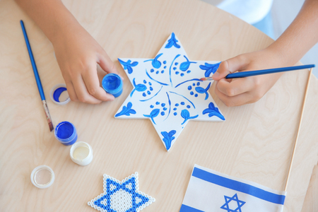 Jewish boy painting up star at home