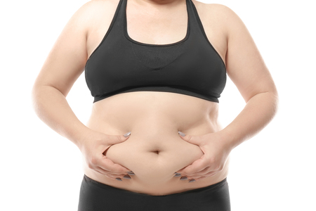 Woman touching fat on her belly against white background. Weight loss concept Stock Photo