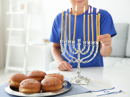 Jewish boy lightning menorah at home