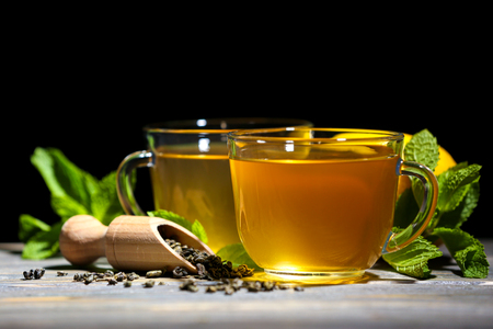 Cups of mint tea on table against black background Stock Photo