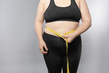 Giovane donna sovrappeso che misura la sua pancia su sfondo grigio. Concetto di perdita di peso