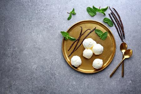 Golden plate with yummy vanilla ice cream on table Фото со стока