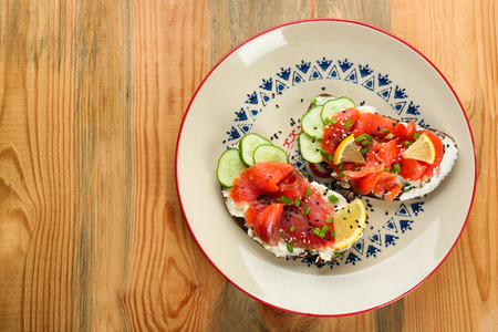 Tasty sandwiches with salmon and lemon on ornate plate