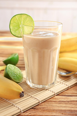 Banana smoothie in glass decorated with slice of lime on wooden table