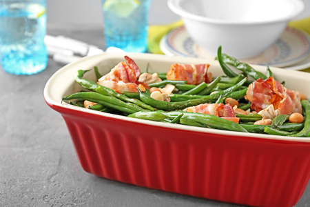 Casserole dish with delicious green beans and fried bacon on table Stock Photo