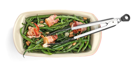 Casserole dish with delicious green beans and fried bacon on white background