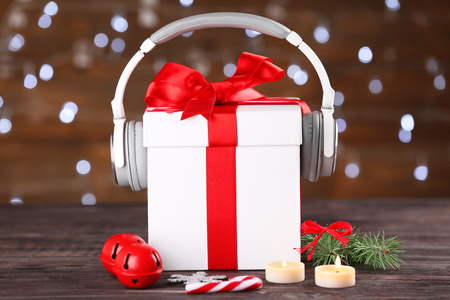Beautiful composition with gift box and headphones on table against blurred lights. Christmas music concept 免版税图像