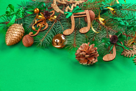 Beautiful composition with fir tree branches and decorations on color background. Christmas music concept