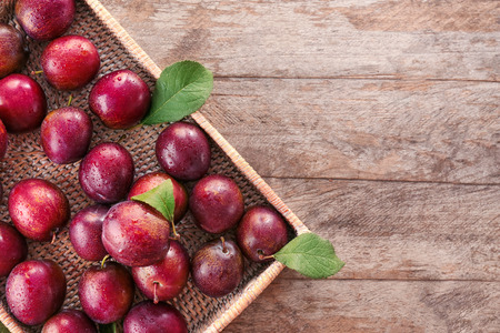 Fresh ripe plums on wicker tray