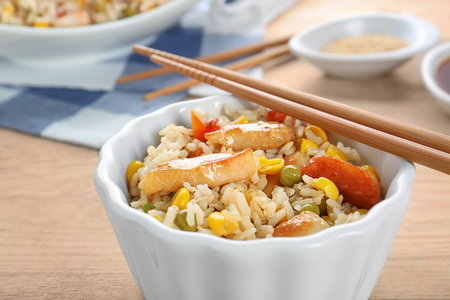 Bowl with tasty brown rice and vegetables, close up