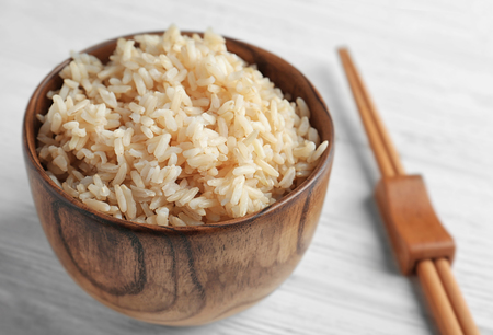 Bowl with brown rice on wooden table