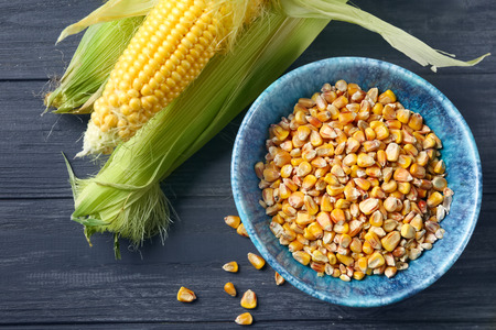 Bowl with kernels and fresh corn cobs on wooden background