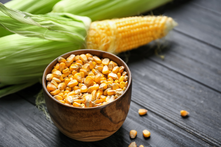 Bowl with corn kernels on wooden background 写真素材