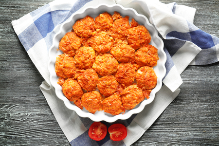 Baking dish with tasty sausage balls on table