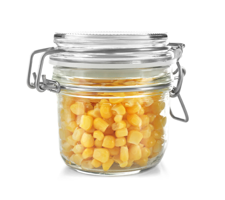 Jar with canned corn kernels on white background 免版税图像