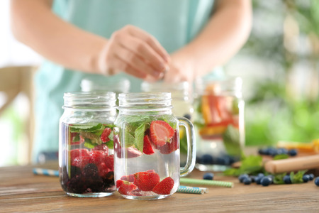 Mason jars of infused water and blurred woman on background 免版税图像
