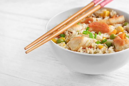 Recipiente con arroz integral, verduras y palillos en la mesa de madera Foto de archivo