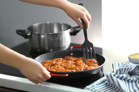 Woman cooking tasty sausage balls on kitchen stove