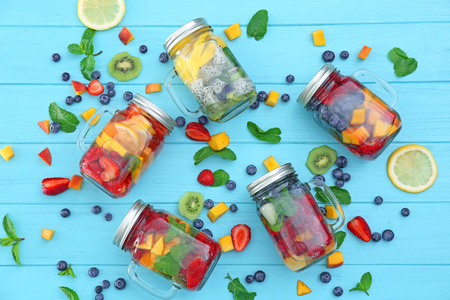Mason jars with fruits and berries on color wooden table