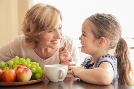 Cute little girl and her grandmother sitting at table