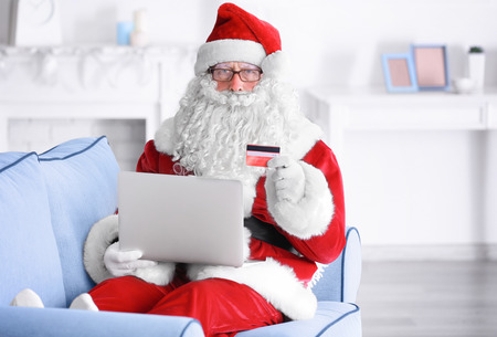 Santa Claus with laptop and credit card on sofa at home
