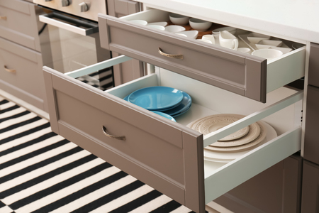 Set of ceramic tableware in kitchen drawers