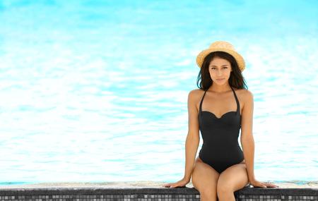 Beautiful young woman in bikini sitting near swimming pool