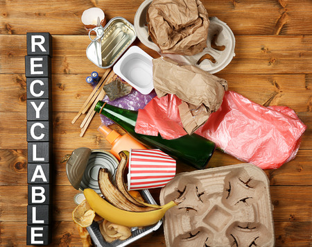 Composition with garbage and word Recyclable on wooden background