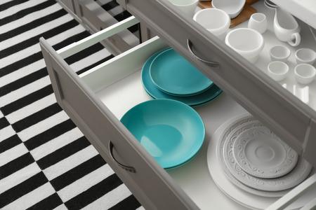 Set di stoviglie in ceramica nei cassetti della cucina Archivio Fotografico