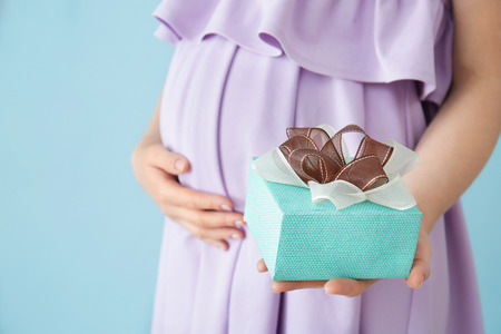 Pregnant woman holding baby shower gift against color background