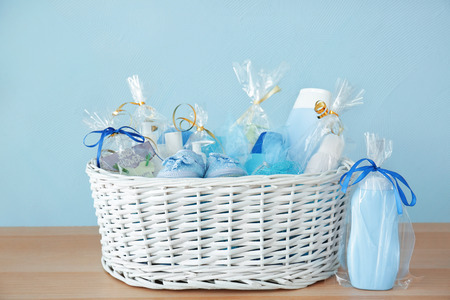 Wicker basket with baby shower gifts on wooden table against color background