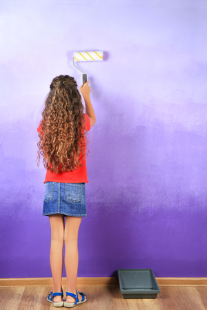 Little cute girl painting wall in room Stock Photo