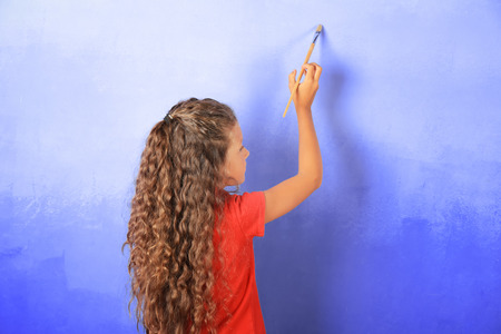 Little cute girl painting wall Stock Photo