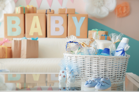 Wicker basket with gifts for baby shower party on table indoors Zdjęcie Seryjne
