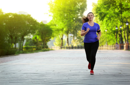 Overweight young woman jogging in park. Weight loss concept Stock fotó