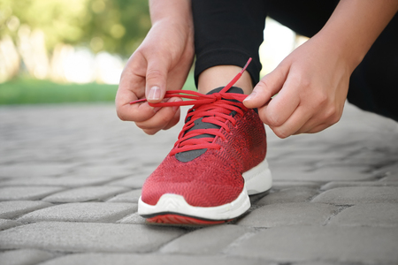 Young woman tying her shoelaces in park, closeup. Weight loss concept