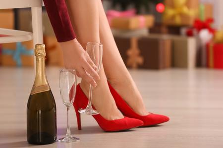 Frau in Schuhen mit hohen Absätzen, die zu Hause ein Glas für Champagner hält