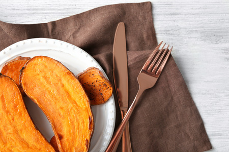 Plate with cooked sweet potato on table