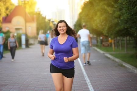 Jeune femme en surpoids faisant du jogging dans la rue. Notion de perte de poids Banque d'images