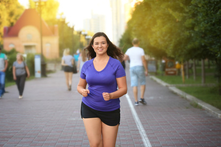 Overweight young woman jogging in the street. Weight loss concept Imagens